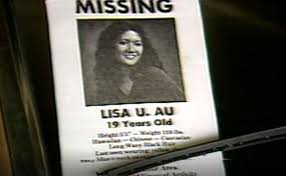 """A poster tucked under a windshield wiper reads """"missing"""" and features a photo of Lisa Au."""