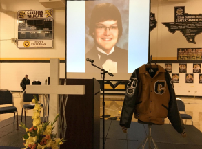 A memorial is pictured inside a high school gymnasium, featuring a photo of Tom Brown, his varsity jacket and an ornamental cross with a floral arrangement.