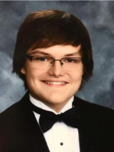 Tom Brown smiles in a formal senior portrait.
