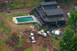 The Pennsylvania house of Hugo Selenski is pictured here, with excavation equipment being used to search the grounds. A dozen sets of charred human remains were discovered buried in Selenski's yard after a criminal accomplice of his tipped off police.
