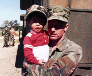 David Cox is pictured with a small child in an undated photo from his period of service with the USMC.