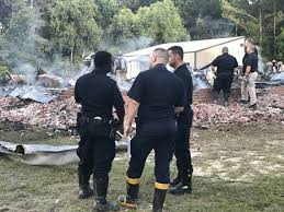 Here, first responders are pictured at the scene of the (extinguished) house fire.