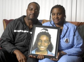 Asha's parents, Harold (left) and Iquilla (right) hold a portrait of their missing daughter.