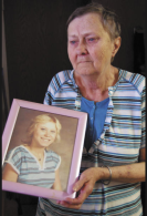 Lori's mother, Sandra, holds a portrait of her only child. Sandra died in 2020, without ever learning who murdered her daughter. The case remains open.